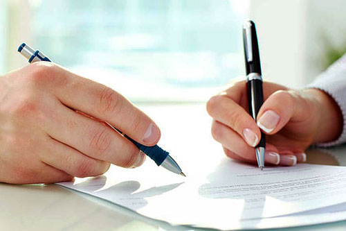 hands writing pen paper contract legal